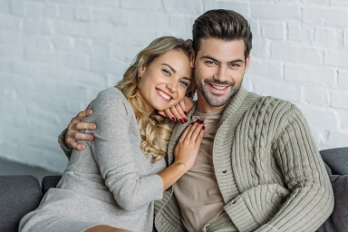 portrait of smiling couple hugging and looking at camera on sofa in living room